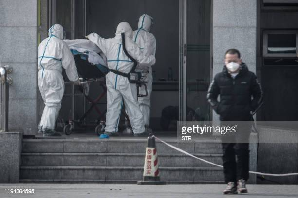 TOPSHOT Medical staff members carry a patient into the Jinyintan hospital where patients infected by a mysterious SARSlike virus are being treated in...