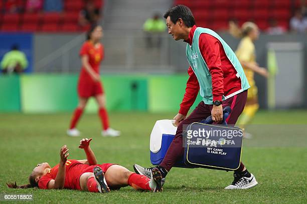 Medical staff members comes onto the pitch to assist a China player during the Women's First Round Group E match between China PR and Sweden on Day 4...