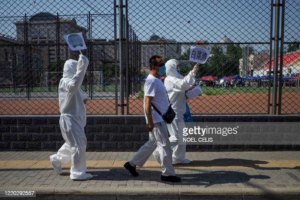 TOPSHOT Medical staff members in full protective gear carry signs to assist people who live near or who have visited the Xinfadi Market a wholesale...
