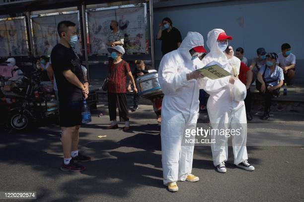 TOPSHOT Medical staff members in full protective gear stand outside the Guangan sports centre to assist people who live near or who have visited the...