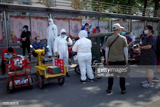 Medical staff members in full protective gear stand outside the Guangan sports centre to assist people who live near or who have visited the Xinfadi...