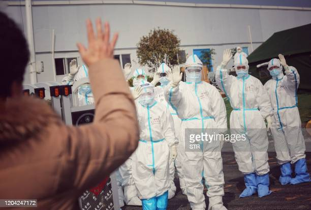 Medical staff members wave to a recovered patient at Leishenshan Hospital the makeshift hospital for the COVID19 coronavirus patients in Wuhan in...