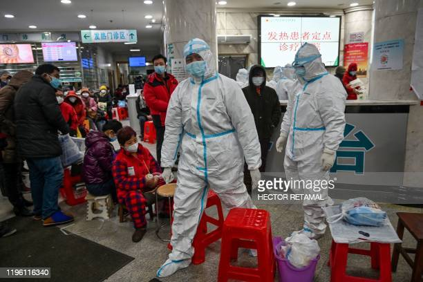 Medical staff members wearing protective clothing to help stop the spread of a deadly virus which began in the city, walk next to patients waiting...