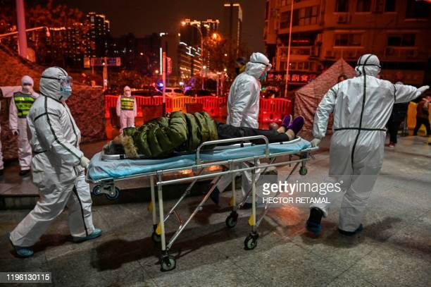 TOPSHOT Medical staff members wearing protective clothing to help stop the spread of a deadly virus which began in the city arrive with a patient at...