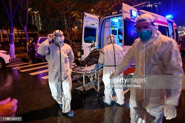 Medical staff members wearing protective clothing to help stop the spread of a deadly virus which began in the city, arrive with a patient at the...