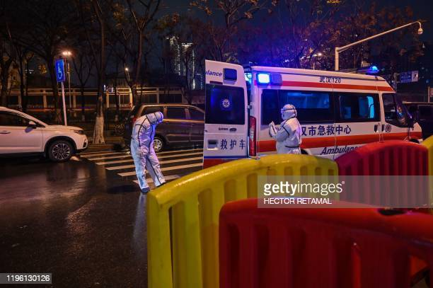 Medical staff members wearing protective clothing to help stop the spread of a deadly virus which began in the city arrive with a patient at the...