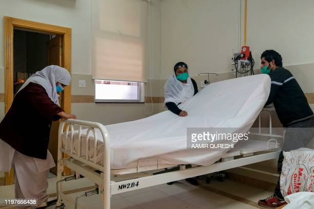 Medical staff members wearing protective masks prepare a room in an isolation ward as a preventative measure following the coronavirus outbreak, at...