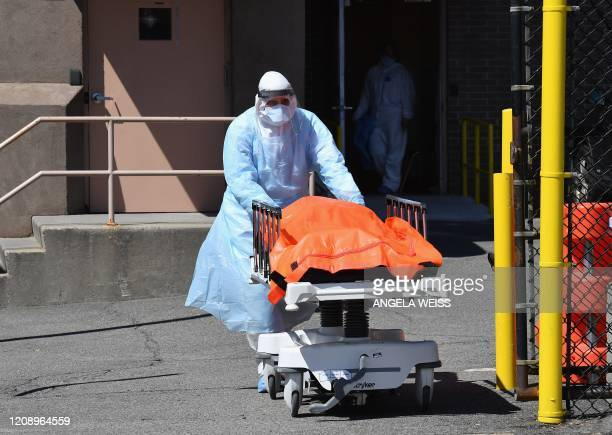 Medical staff move bodies from the Wyckoff Heights Medical Center to a refrigerated truck on April 2, 2020 in Brooklyn, New York. - The Federal...