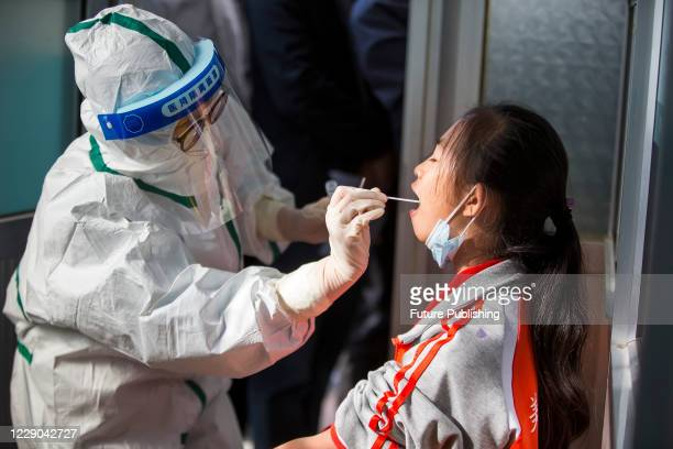 Medical staff perform nucleic acid test on a child who has recently been to Qingdao, Binzhou City, Shandong Province, China, October 13, 2020.-...