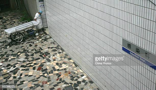 Medical staff pulls a bed to a isolation ward of the infection department at the Ziyang First People's Hospital on July 26, 2005 in Ziyang of Sichuan...