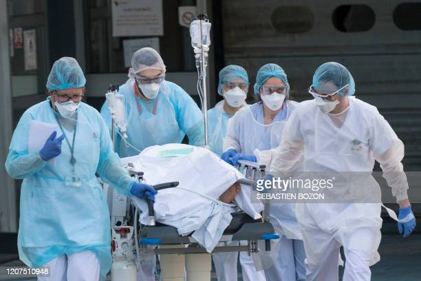 TOPSHOT Medical staff push a patient on a gurney to a waiting medical helicopter at the Emile Muller hospital in Mulhouse eastern France to be...