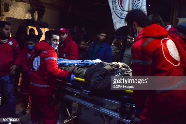 DOUMA DOUMA SYRIA DAMASCUS SYRIA Medical staff seen helping a patient to as he was being transferred to the ambulance The evacuation of two wounded...