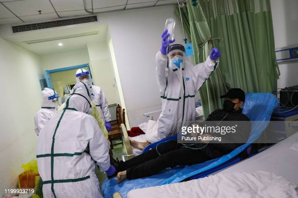 Medical staff settle down a 2019-nCoV patient just moving into the isolation ward in a hospital in Wuhan in central China's Hubei province Thursday,...