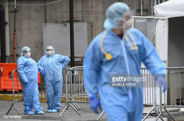 Medical staff stand outside a COVID19 screening tent of the Brooklyn Hospital Center on March 20 2020 in the Brooklyn borough of New York