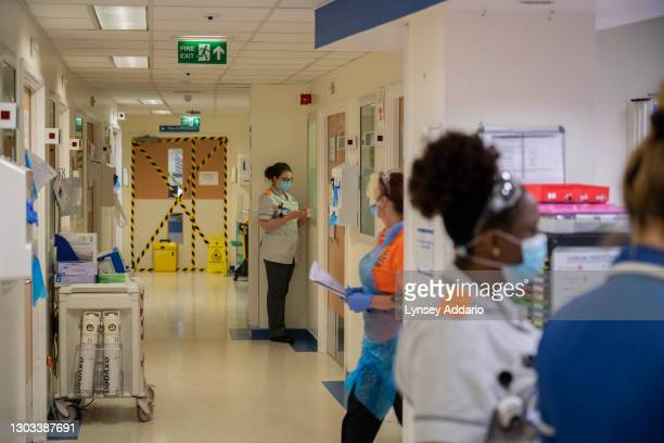 Medical staff stand outside rooms of suspected COVID patients in the A&E at the University Hospital Coventry on May 25, 2020 in Coventry, United...