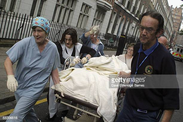 Medical staff stretcher a victim away from Russell Square underground station after a series of explosions ripped through London's transport network...