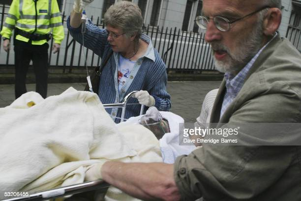 Medical staff stretcher away an injured man from Russell Square underground station after a series of explosions ripped through London's transport...