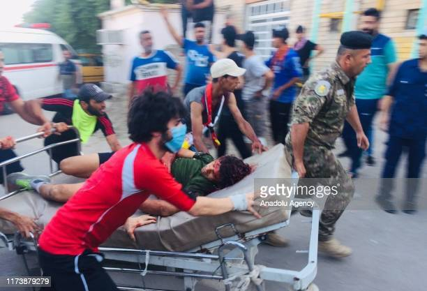 Medical staff take injured protestors to a hospital after intervention of the security forces in demonstrations in capital Baghdad's Palestine Street...