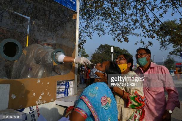 Medical staff take nasal swab for Covid Rapid Antigen Test from Hindu devotees as they arrive to take a holy dip in the waters of the River Ganges on...