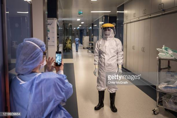 Medical staff take photographs dressed in personal protective equipment before taking part in a tracheotomy operation on a patient infected with the...