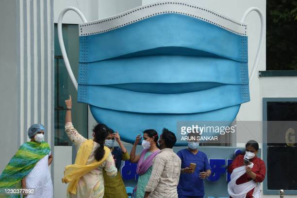 Medical staff take pictures beside a large replica facemask displayed as an awareness campaign against the Covid-19 coronavirus, in Chennai on...