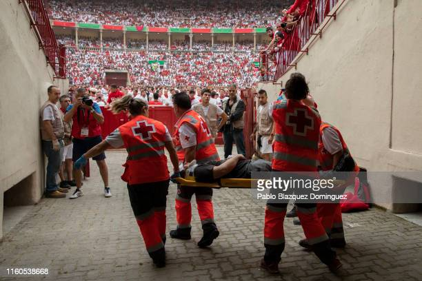 Medical staff takes care of an injured reveller who ran with the Puerto de San Lorenzo's fighting bulls during the second day of the San Fermin...