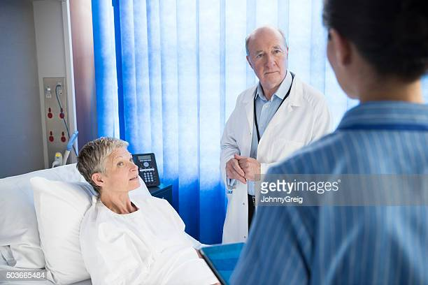 Medical staff talking to female patient in hospital bed