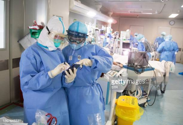Medical staff treat check a mobile phone as they treat COVID19 coronavirus patients at a hospital in Wuhan in China's central Hubei province on March...