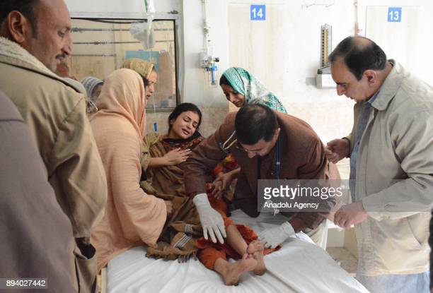 A medical staff treats a woman injured in a suicide attack at Bethel Memorial Methodist Church as her relatives try to calm her down in Quetta...