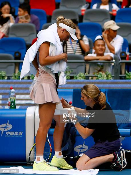 A medical staff treats Caroline Wozniacki of Denmark reacts during the game against Anna Karolina Schmiedlova of Slovakia in day 3 of 2015 Dongfeng...