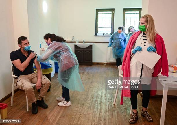 "Medical staff vaccinates a man during the vaccination marathon organized at the ""Bran Castle"" in Bran village on May 8, 2021. - Romanian authorities..."