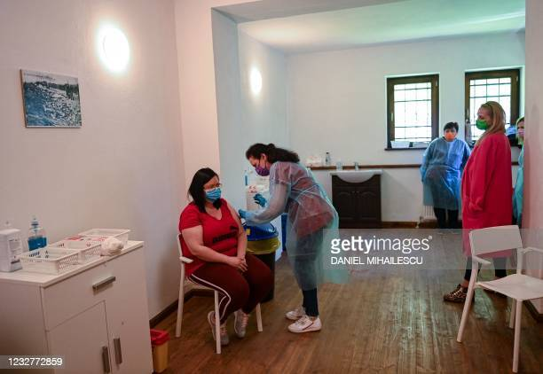 "Medical staff vaccinates a woman during the vaccination marathon organized at the ""Bran Castle"" in Bran village on May 8, 2021. - Romanian..."