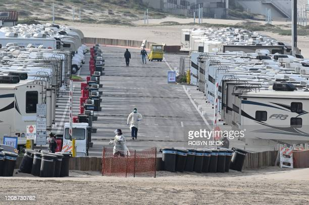 Medical staff walk among RV campers in a beachside parking lot being used as an isolation zone for people with COVID-19, on March 31 at Dockweiler...
