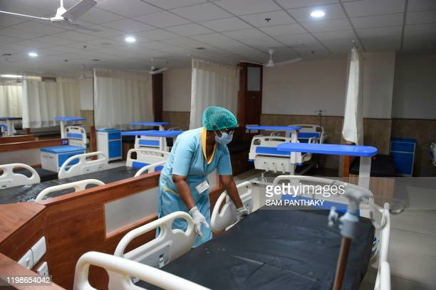 A medical staff wearing a protective facemask arranges a bed inside an isolation ward opened as a preventative measure following a SARSlike virus...