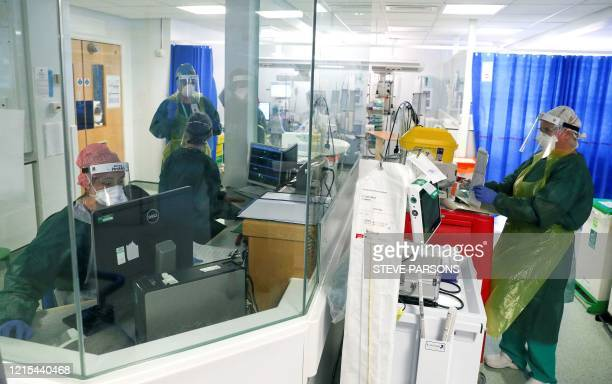 Medical staff wearing full PPE , including a face mask, long aprons, and gloves as a precautionary measure against COVID-19, work on an Intensive...