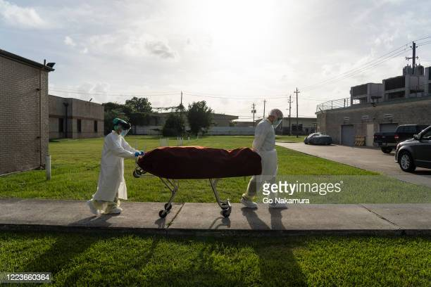 Medical staff wearing full PPE push a stretcher with a deceased patient to a car outside of the Covid19 intensive care unit at the United Memorial...