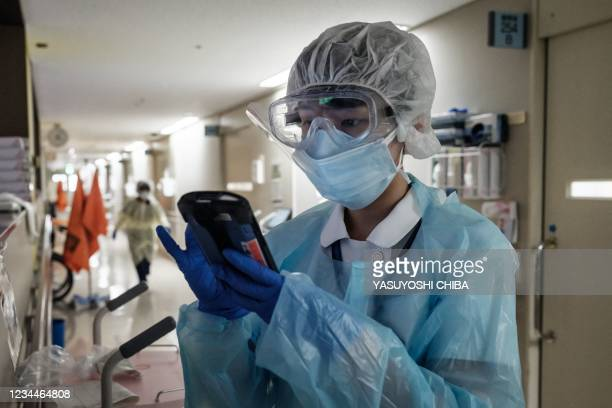 Medical staff wearing personal protective equipment checks data of a Covid-19 patient on a device at Hokkaido University Hospital in Sapporo on...