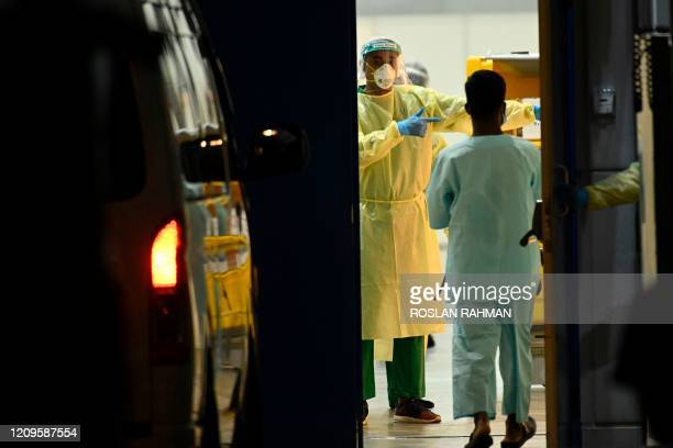 Medical staff wearing Personal protective equipment wait for patients to be transferred to a temporary hospital as a preventive measure against the...