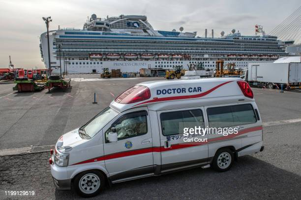 Medical staff wearing protective clothing take a passenger diagnosed with coronavirus to hospital after removing them from the Diamond Princess...