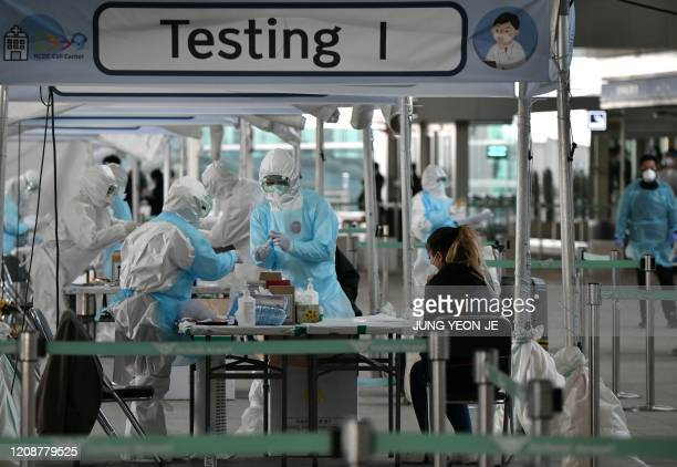 TOPSHOT Medical staff wearing protective clothing take test samples for the COVID19 coronavirus from a foreign passenger at a virus testing booth...