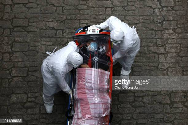 Medical staff wearing protective gear move a patient infected with the coronavirus from an ambulance to a hospital on March 09 2020 in Seoul South...