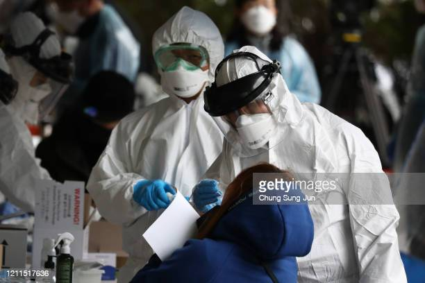 Medical staff, wearing protective gear, take samples from people at a building where 46 people were confirmed to have the coronavirus , at a...