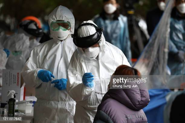 Medical staff wearing protective gear take samples from people at a building where 46 people were confirmed to have the coronavirus at a temporary...