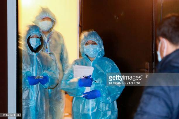 Medical staff wearing protective suits are seen at a road block at the entrance to the city of Almaty late on March 18 2020 Kazakhstan's two largest...
