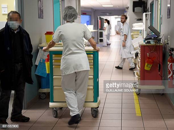 Medical staff work as a patient stands in a corridor at the emergency department of the hospital of Trousseau in Tours on January 12 2017 during a...