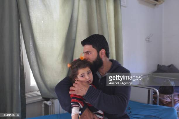 A medical staff Zayn alAbidin holds a chemical gas attack survivor girl who receives medical treatment during an exclusive interview at an hospital...