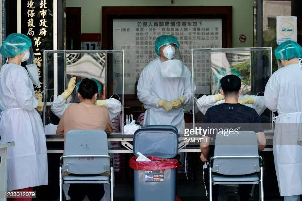 Medical staffers collect samples from local residents during a COVID-19 corona virus testing at the Xindian District in New Taipei City on May 21,...
