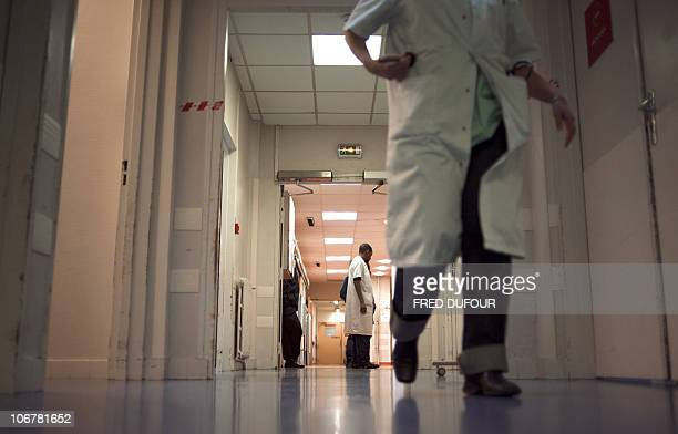 Medical staffers walk on November 9 2010 in a corridor of the Hopital Tenon in Paris The employees of the urgency department of the hospital are on...