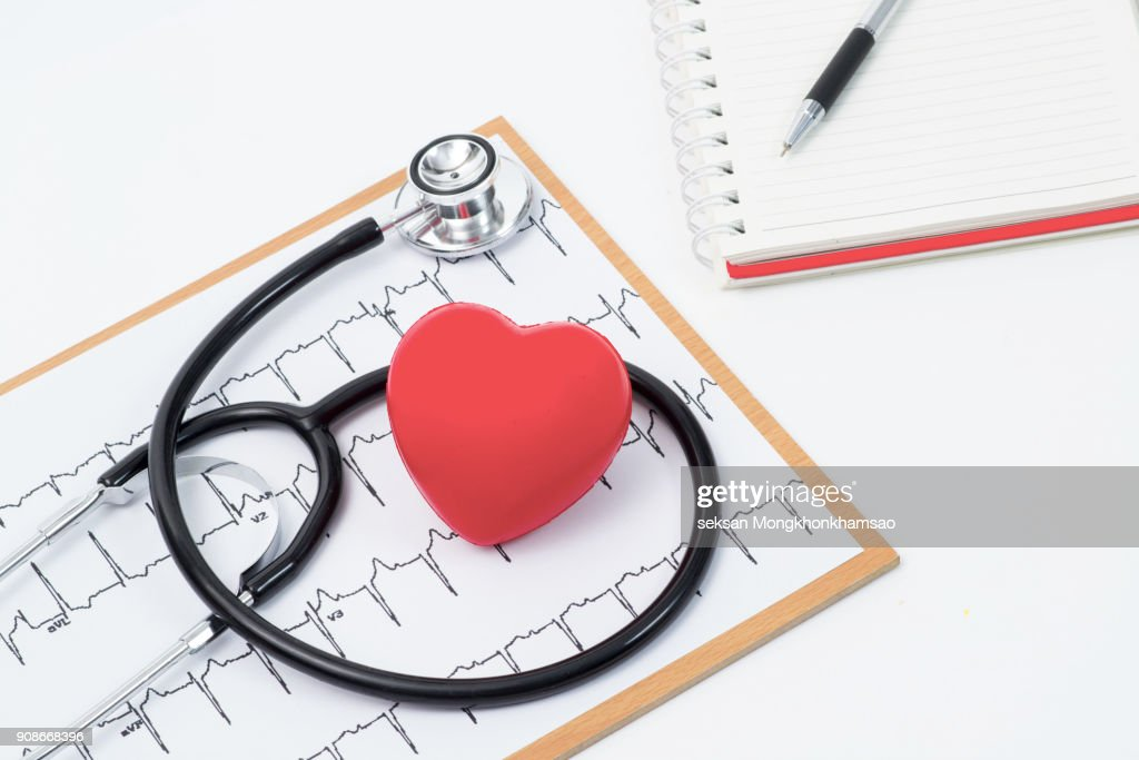 Medical stethoscope head and red toy heart lying on cardiogram chart closeup. Cardio therapeutist, pulse graph, cardiac physical, heart rate measure, arrhythmia, 911, er and resuscitation concept : Stock Photo