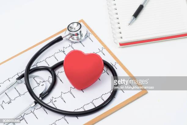 medical stethoscope head and red toy heart lying on cardiogram chart closeup. cardio therapeutist, pulse graph, cardiac physical, heart rate measure, arrhythmia, 911, er and resuscitation concept - cardiac arrhythmia stock pictures, royalty-free photos & images